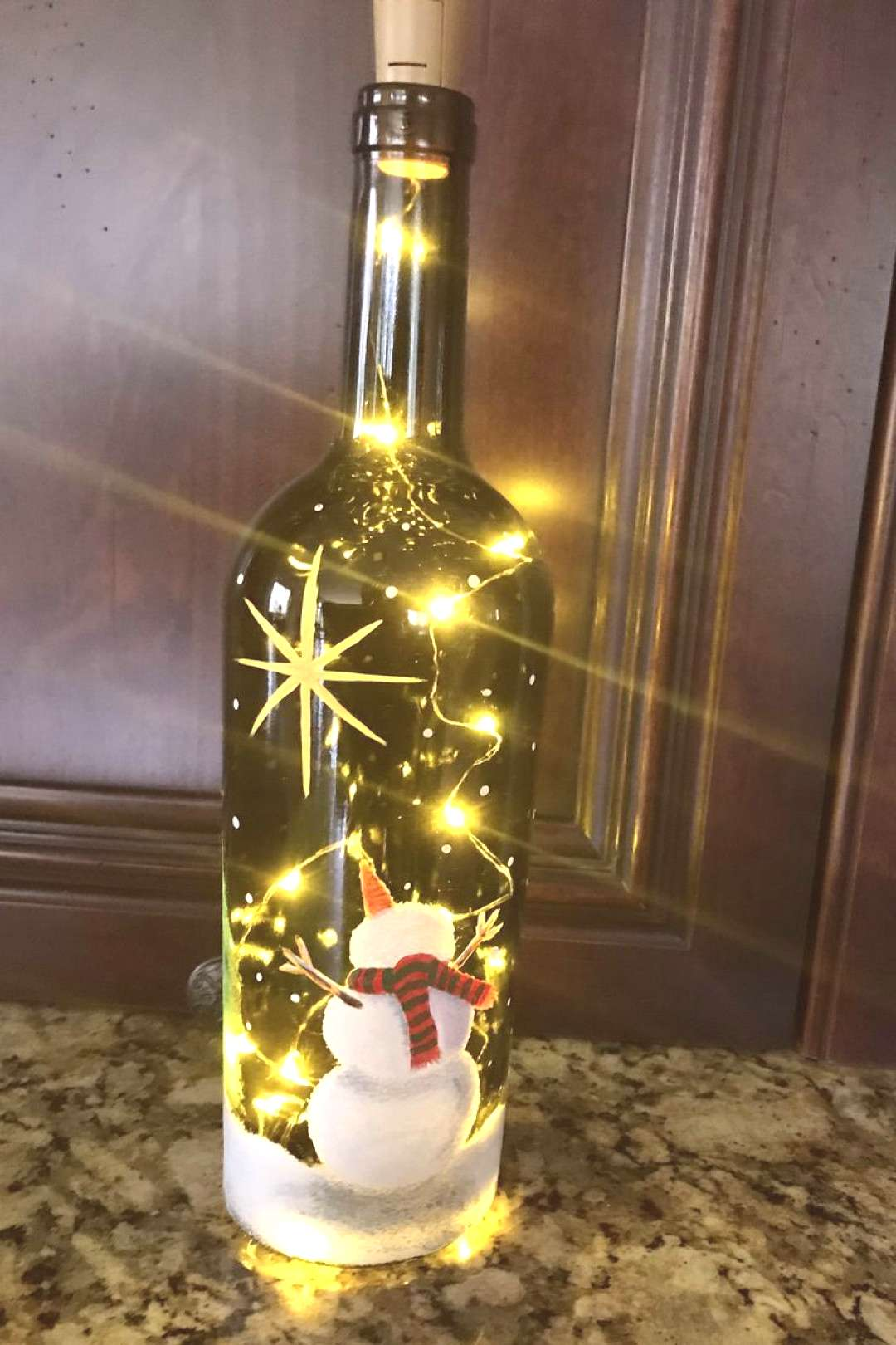 Snowman painted on bottle with fairy lights inside...first bottle I've painted... -